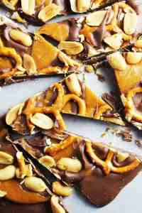 Milk chocolate, caramel, peanuts and pretzel chocolate bark on wax paper