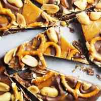 Milk chocolate, caramel, peanuts and pretzel chocolate bark on wax paper