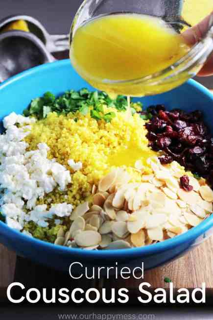 Lemon dressing being poured over a big blue bowl curried couscous salad ready to be tossed