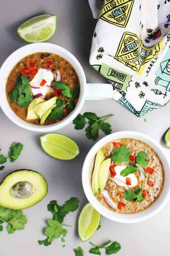 Two bowls of vegetarian black bean soup garnished with avocado, sour cream, cilantro, lime and red pepper