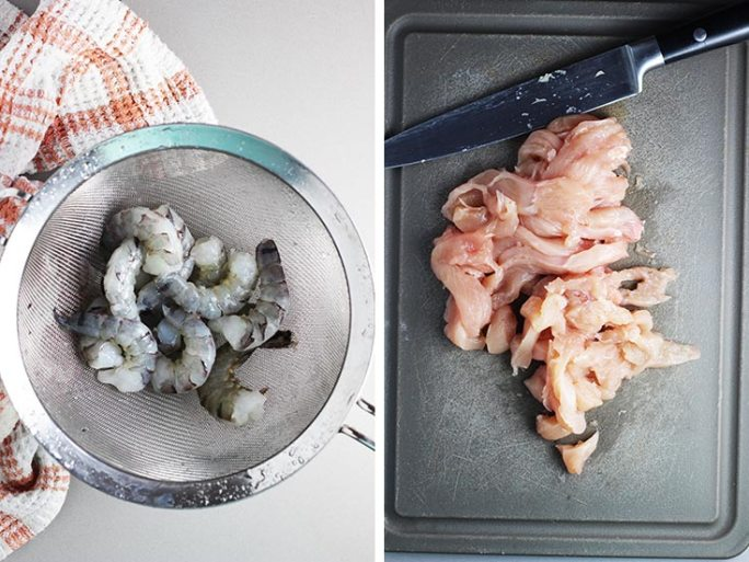 Raw shrimp in a colander and raw chicken sliced on a cutting board