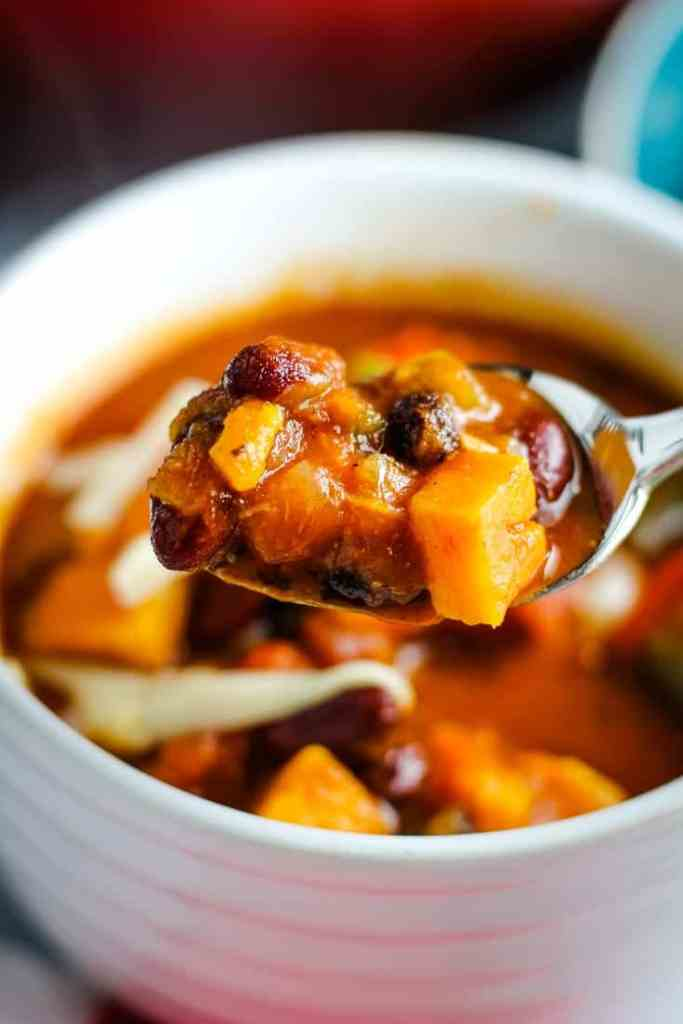 A spoonful of vegetarian sweet potato chili over a bowlful.