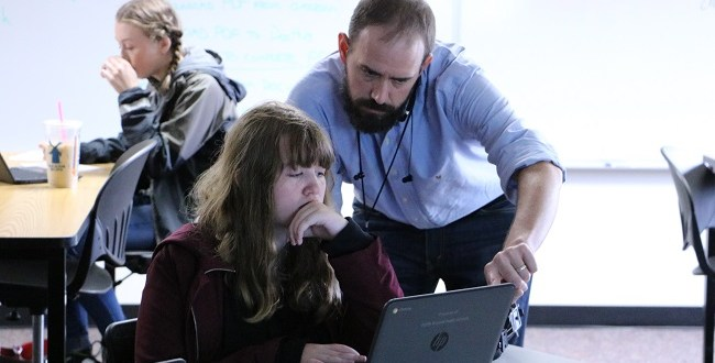 Student and teacher viewing laptop