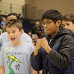 Two middle school boys excitedly watch their robot perform in the competition.