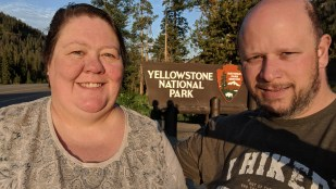 Morning sunrise at the East entry of Yellowstone National Park, Barb and Jason taking that classic tourist photo