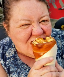 Barb enjoying the scrumptious Lobster Bacon Macaroni and Cheese in a warm bread cone at Taste Track in Epcot Center during the 2019 Festival of the Arts