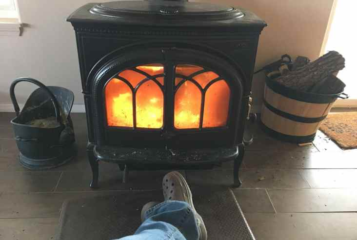 crossed feet in front of a roaring wood stove