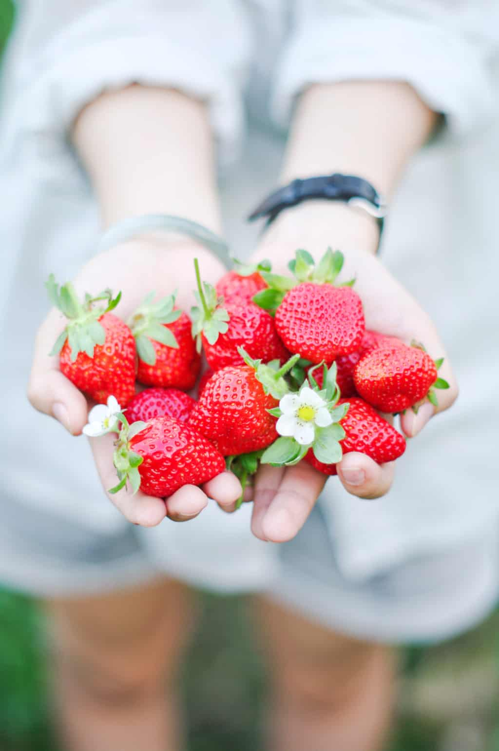 a woman holding out a handful of strawberries