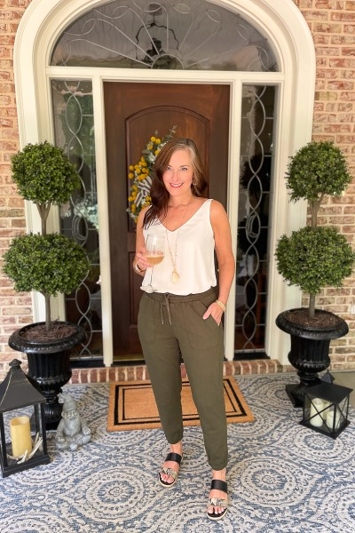 woman in green jogger on porch
