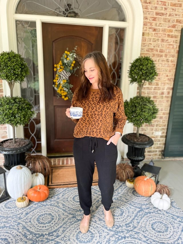 woman on porch dressed in leopard sweatshirt and joggers