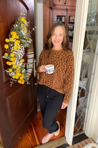 woman standing in doorway with mug