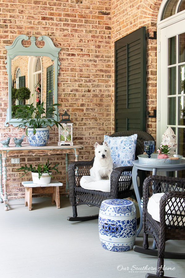 summer front porch with rockers and a white dog