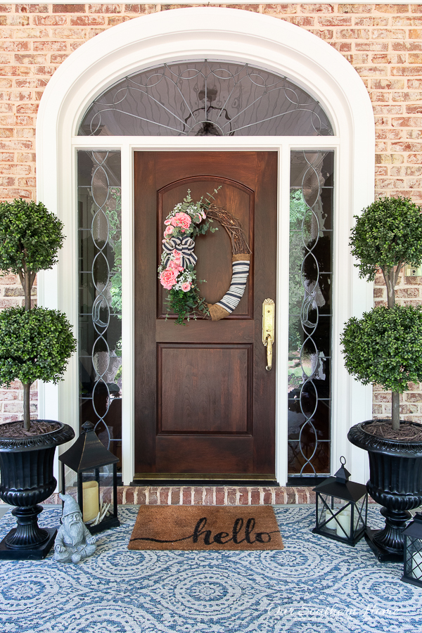 front door with topiaries and rug