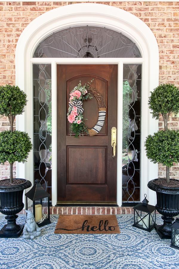 front door with topiaries and rug
