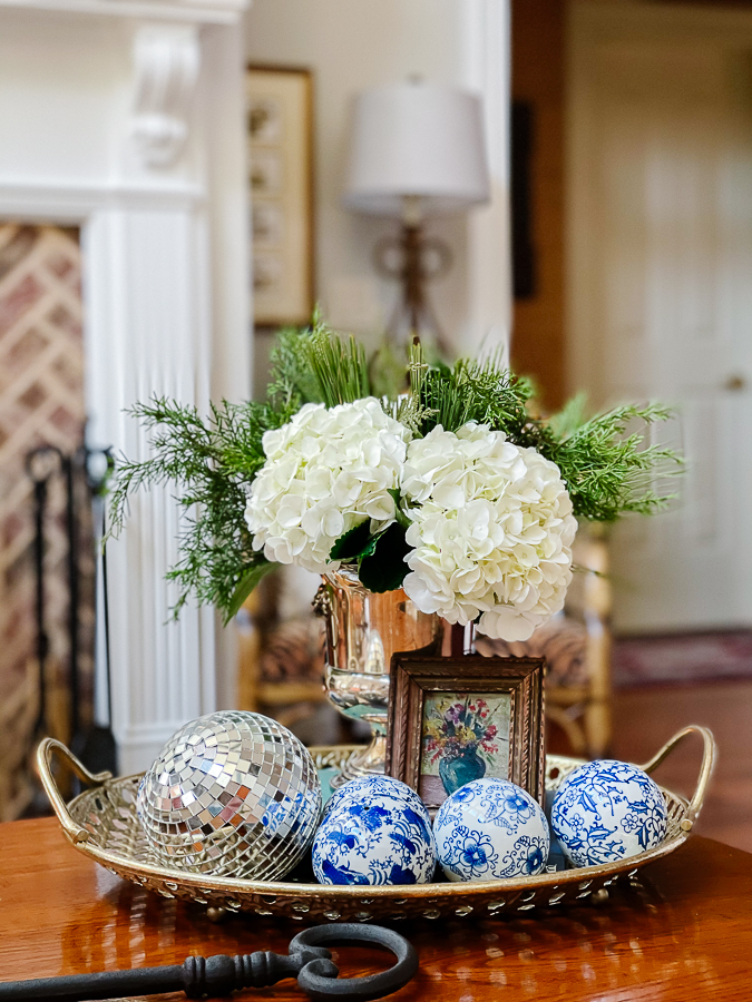 winter floral arrangement with blue and white porcelain balls and small oil