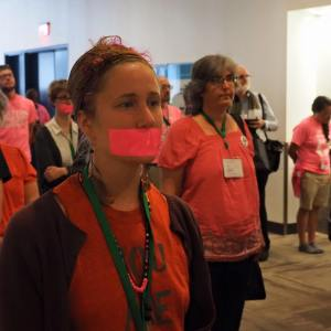 Rachel Halder stands with pink duct tape over her mouth in silent protest with other Pink Menno's on Thursday afternoon, after the Membership Guidelines resolution was passed.