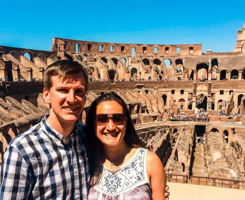 A couple posing and smiling inside the Colosseum