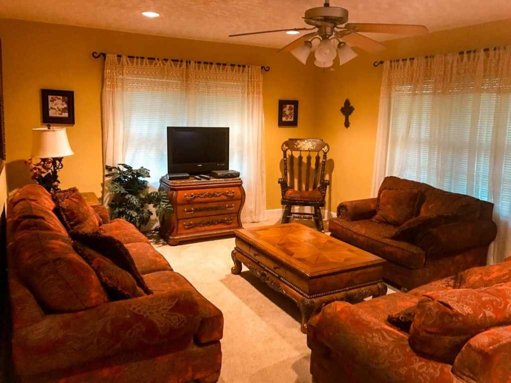 Inside a rental house in Fredericksburg, Texas of the living room with three couches, center table and TV.