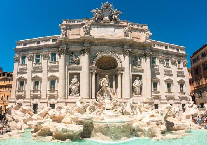 A bright panorama photo of the Trevi Fountain in Rome.