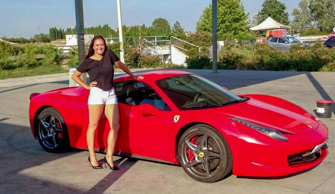 A woman dressed nice in short white shorts, black shirt and high heels next to a red Ferrari in Italy.