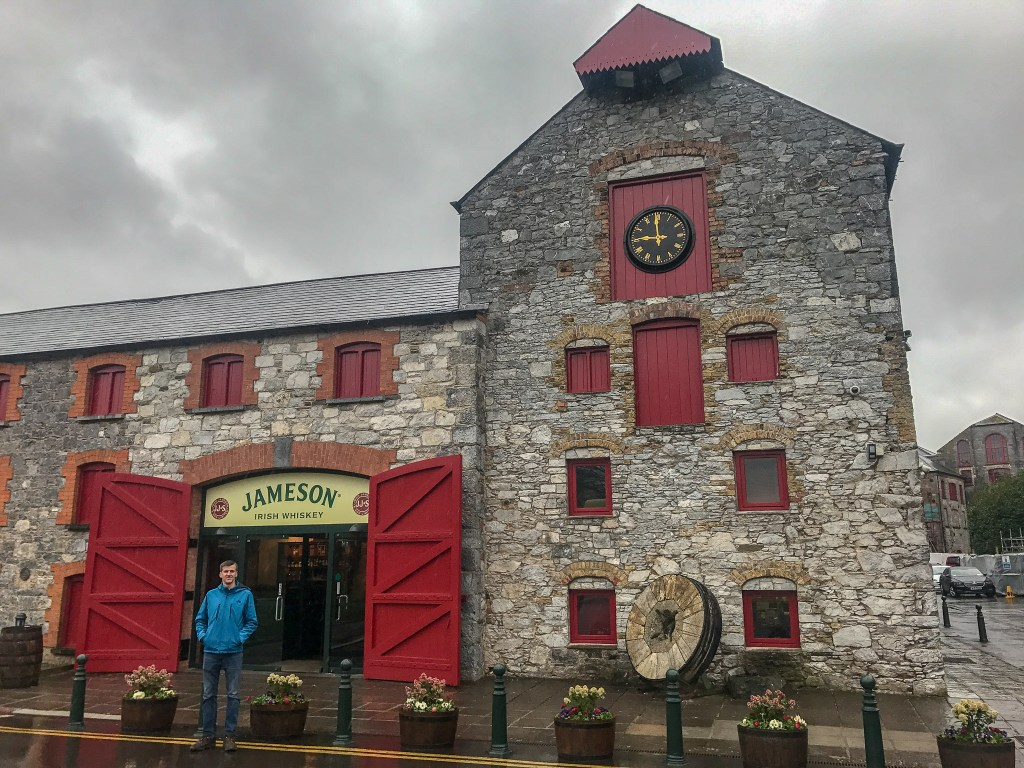A guy standing in front of a Jameson building in Cork, Ireland - one of the best things to do during your 7 days in Ireland.