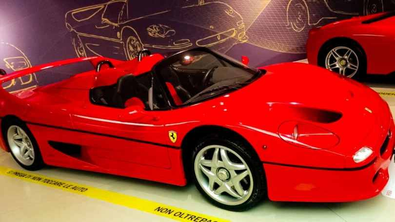 A red convertible Ferrari parked inside the Ferrari Museum in Modena, Italy.