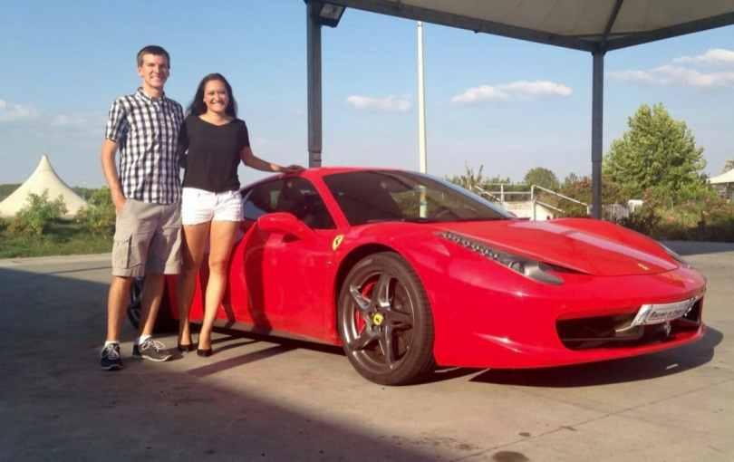A couple standing next to a red Ferrari 458 at a race track in Italy.