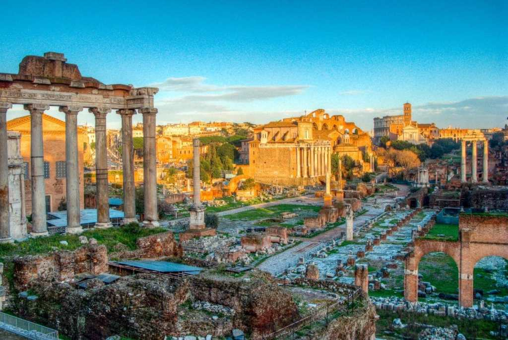 Gorgeous photo of the sunrise at the Roman Forum - ruins of giant columns standing tall and archways.
