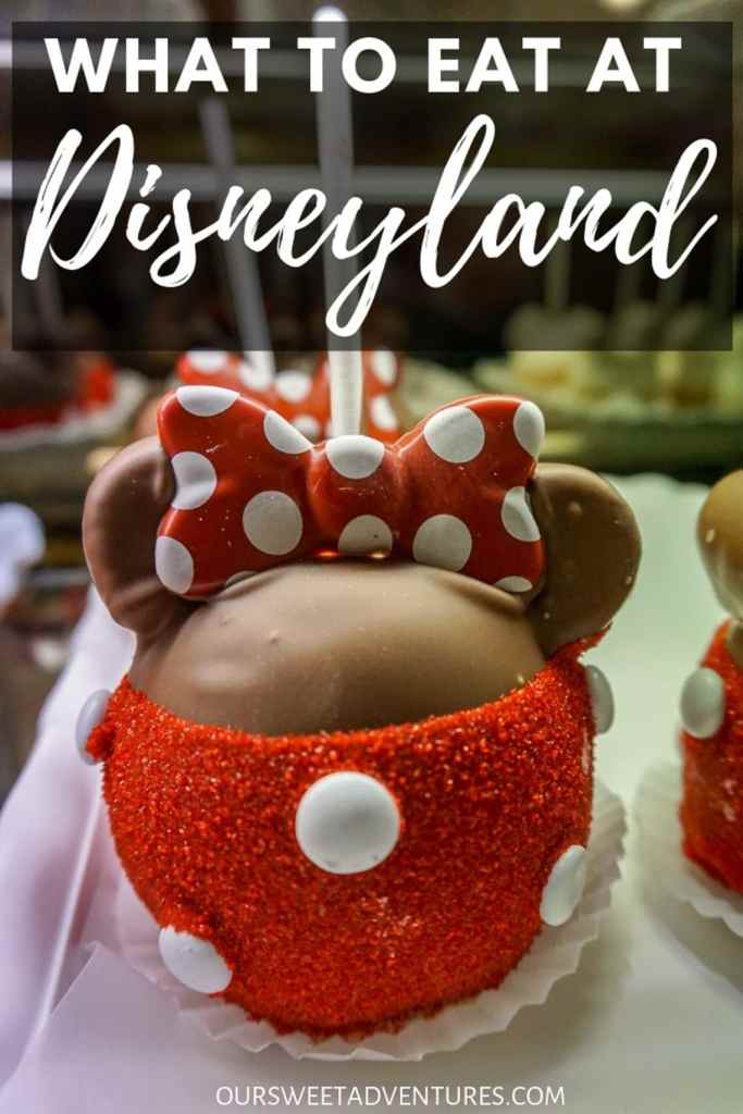 """A chocolate caramel apple with red sugar sprinkles on the bottom with white M&Ms and a bow to resemble Minnie Mouse with text overlay """"What to Eat at Disneyland"""""""