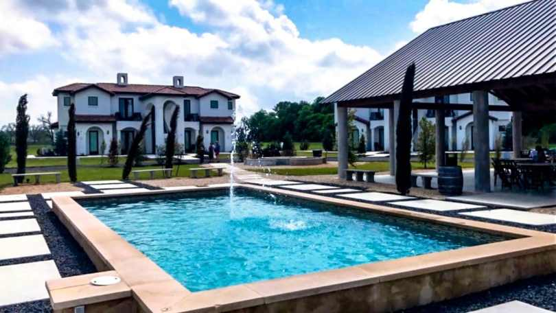 Beautiful rectangle pool with a little fountain and an European villa and covered patio from Barons Creek Vineyard in Fredericksburg, Texas.