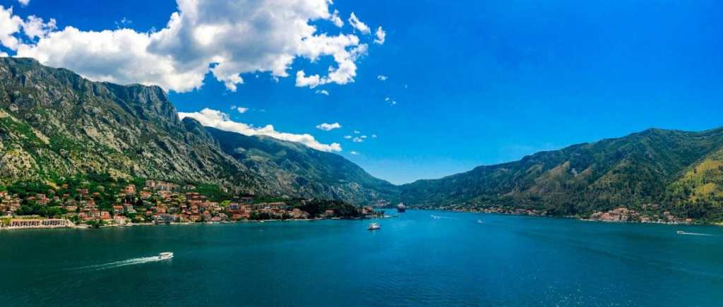 Landscape photo looking out into Bay of Kotor with green mountains surrounding the water.