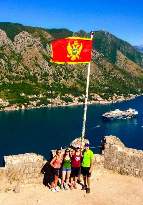 A group of four (three girls and one guy) standing at Kotor's fortress with the Montenegro flag towering over them and the Bay of Kotor with a cruise ship in the background.