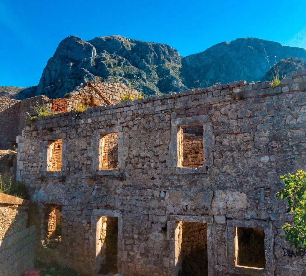 Kotor's castle ruins of a 6th century stone wall with small rectangle windows.