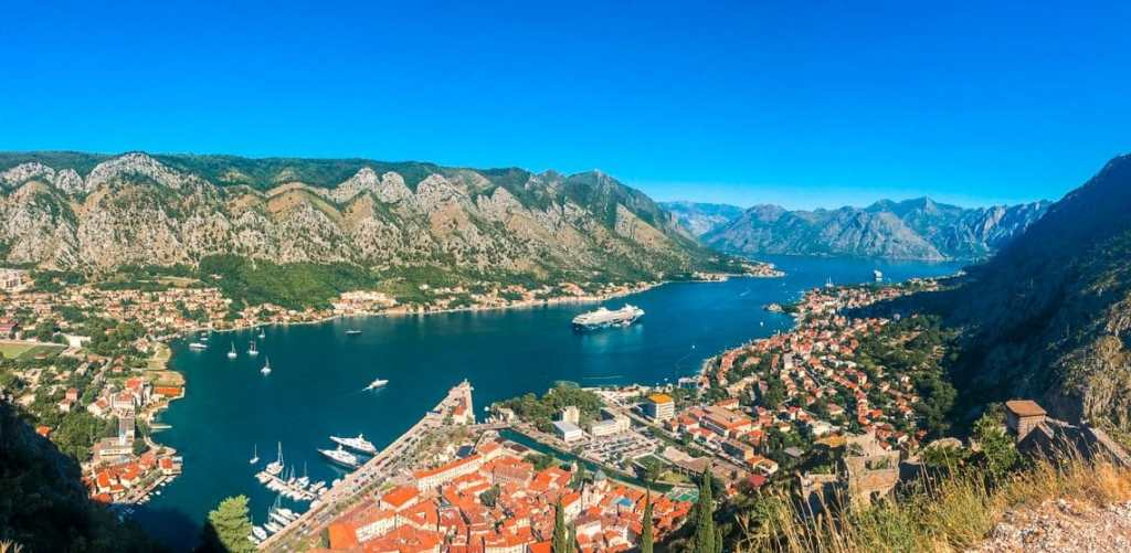Panorama picture from the top of Kotor's castle - the Castle of San Giovanni looking down at the Bay of Kotor and Old Town Kotor in the shape of a triangle leading into the deep blue ocean with mountains hovering over.