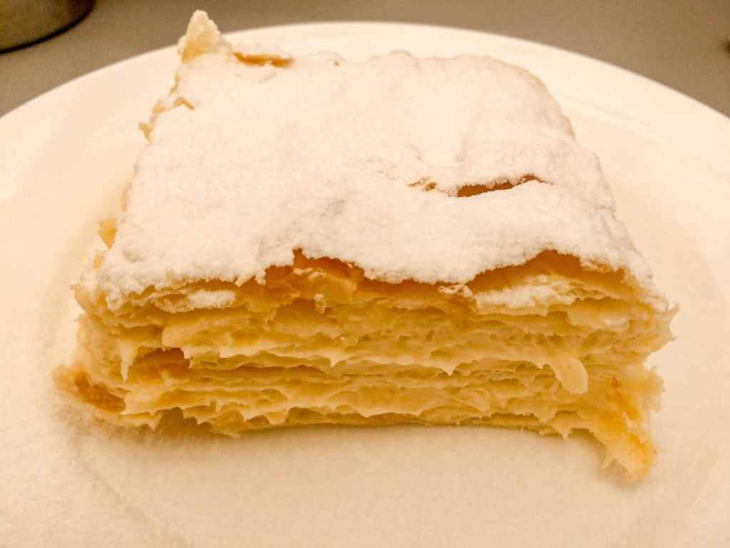 A square piece of krempita with sweet cream filled between layers of flaky puff pastry dough and covered in powdered sugar.
