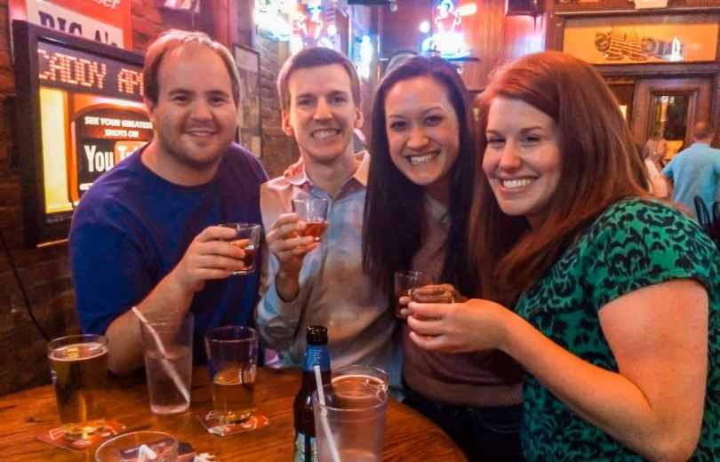 Four friends smiling for a photo and toasting with shot glasses at Big A's.