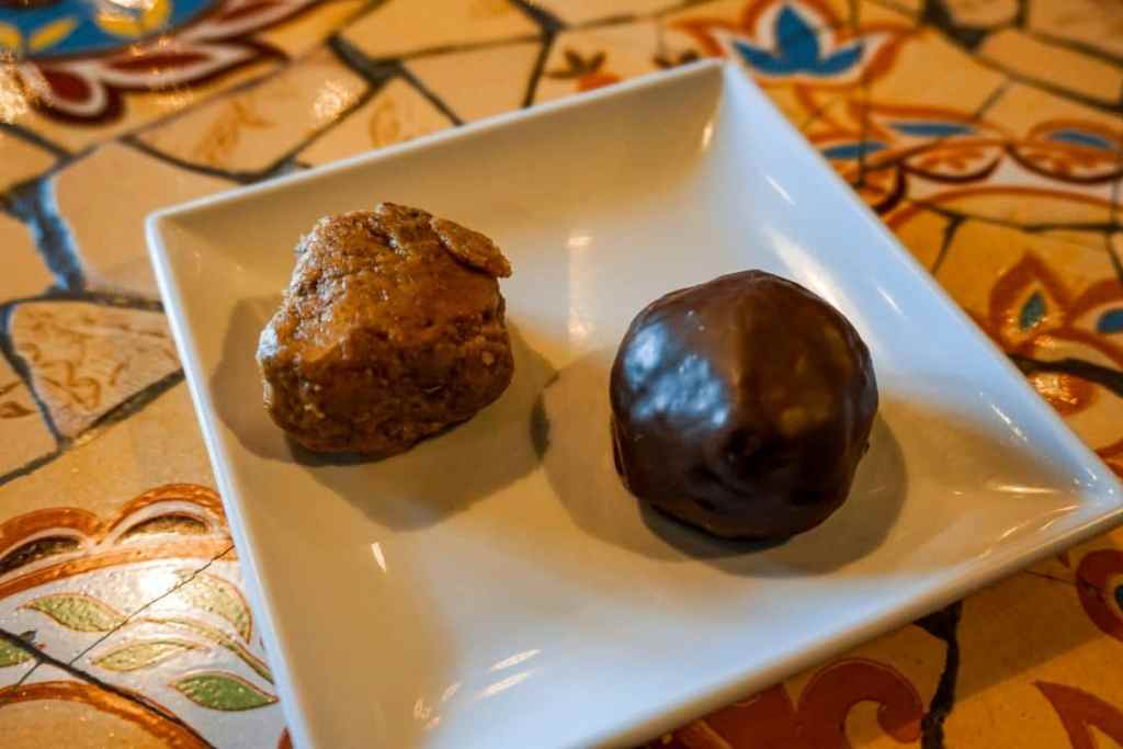 Two peanut butter dessert balls on a white square plate. The one on the right is covered in dark chocolate while the left one is not.