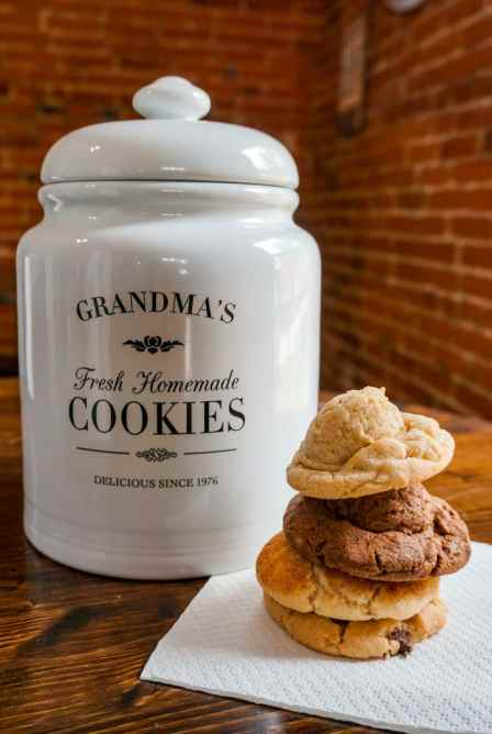 A white cookie jar labeled Grandma's Cookies with a stack of four cookies to the right of the jar.
