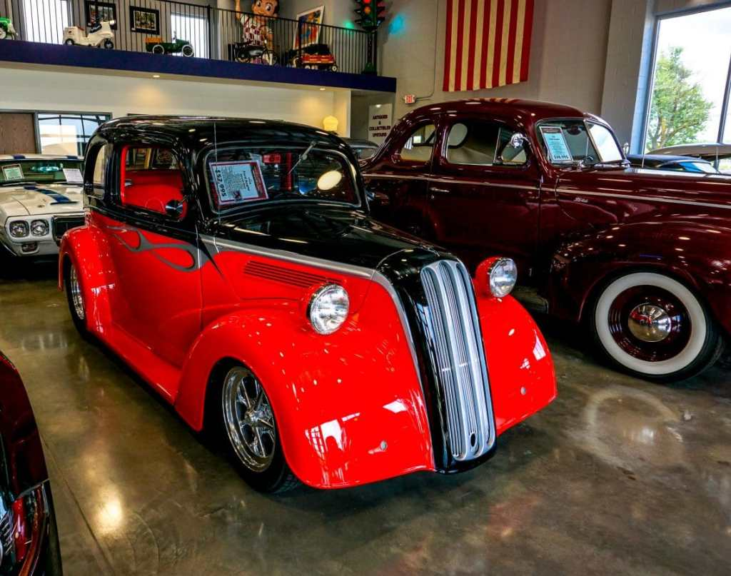 A classic red and black car in a showcase room.