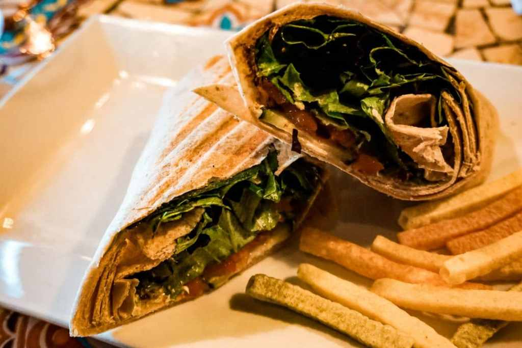 A veggie wrap with a side of veggie straws on a plate.
