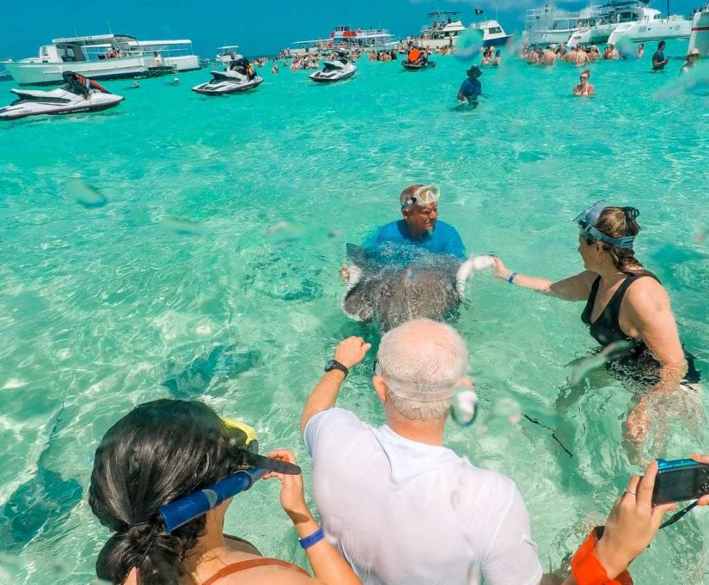 A few people gathered around stroking a stingray at Stingray City with more people and boats in the distance.