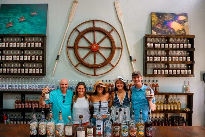 A group family photo of five at Cayman Spirits with bottles of alcohol in front of them.