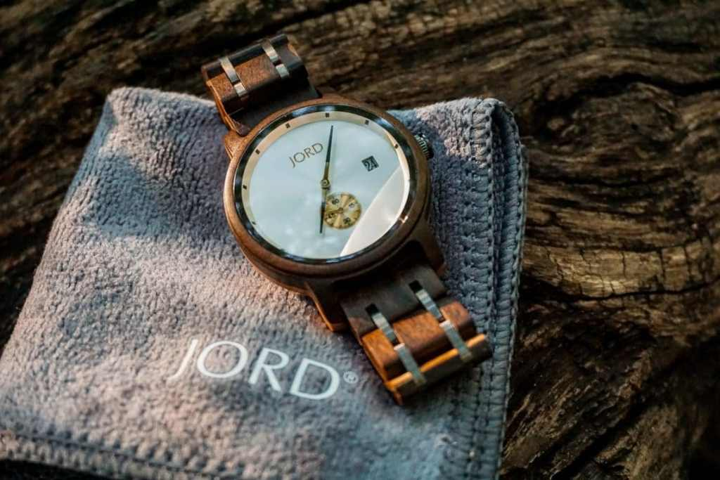 A JORD Hyde wooden watch laying at an angle on the corner of a gray square cloth resting on a wooden log.