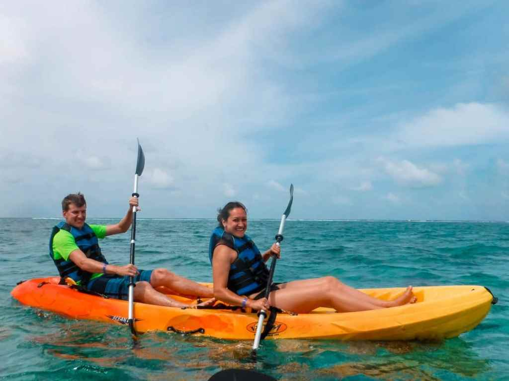 A couple inside an orange and yellow double kayak paddling in the blue ocean.