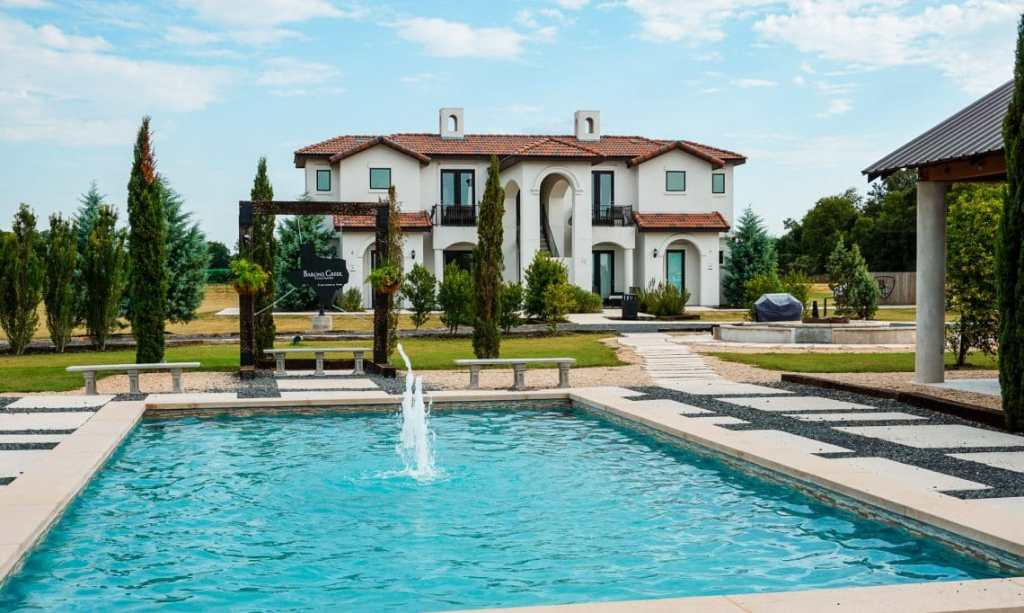 Gorgeous view of a fountain with a European villa in the backyard from Barons Creek Vineyard in Fredericksburg, Texas.