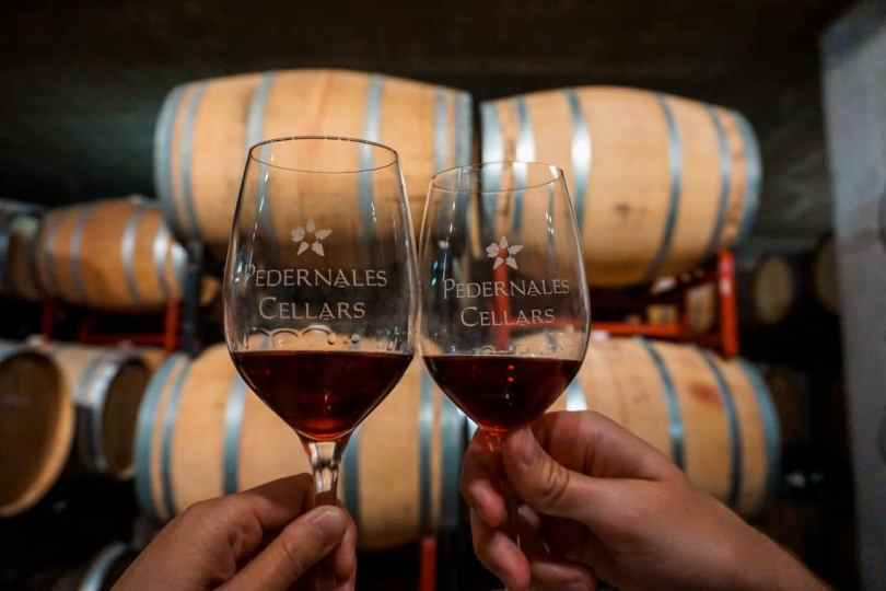Two glasses of red wine from Pedernales Cellars clinking together with barrels in the background.