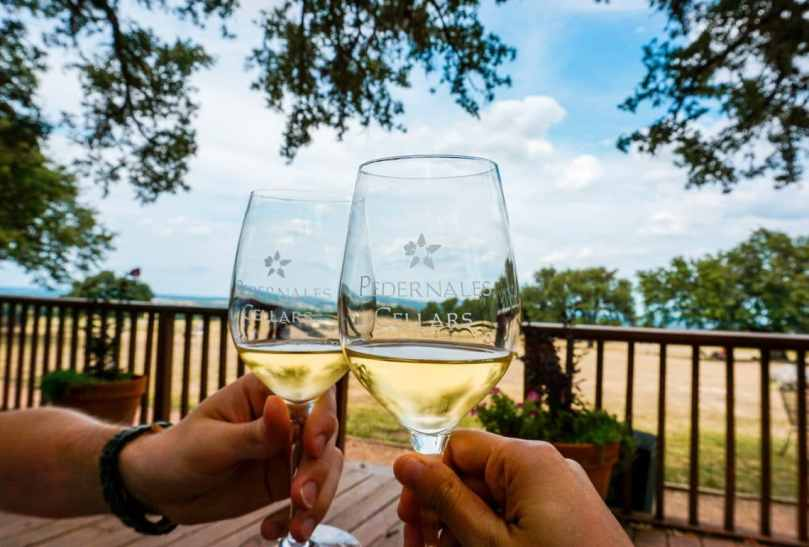 Two glasses of white wine from Pedernales Cellars clinking together with a beautiful scenery of the Texas Hill Country in the backdrop.