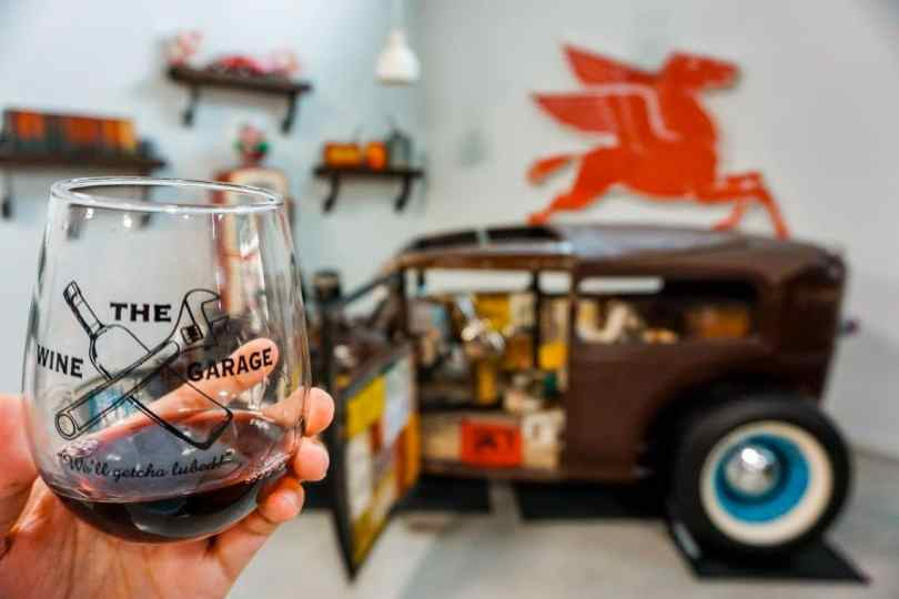 A stemless glass of red wine with a classic Rat Rod in the background from The Wine Garage - one of the best wineries in Fredericksburg.