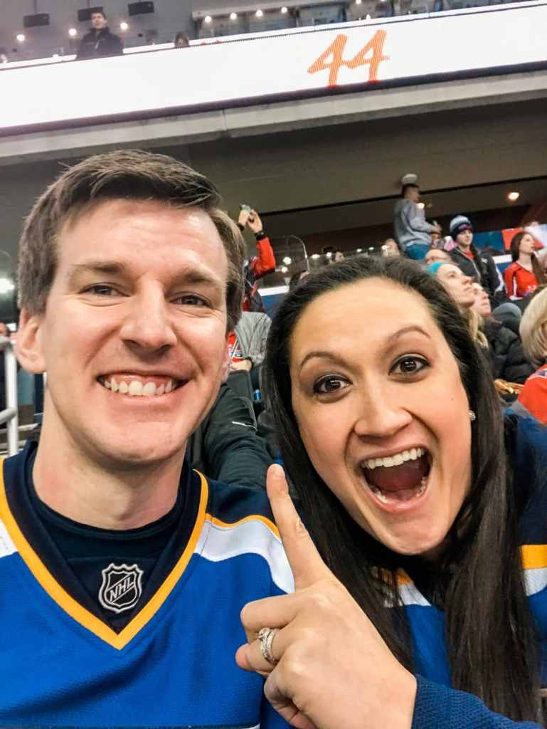 A St. Louis Blues couple cheering on their favorite team inside the Capital One Arena.