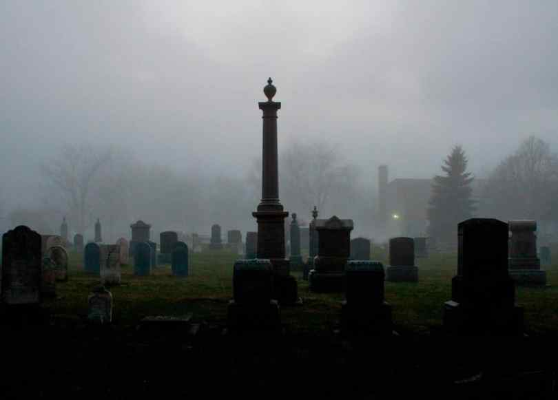 A creepy cemetery with tombstones and a rolling fog.